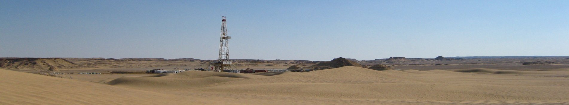 Rig and wellsite view from afar in the desert dunes